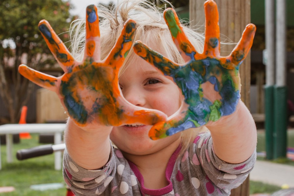 happy and confident young child with painted hands