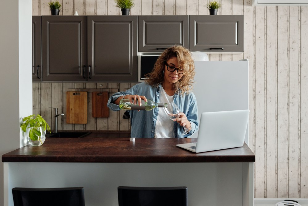 woman pouring wine in front of laptop