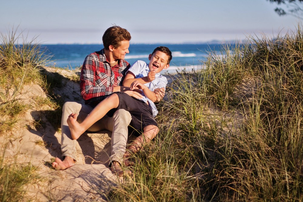 single dad and child having fun at beach