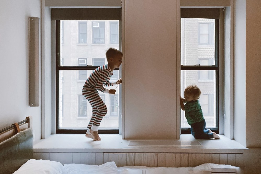 kids jumping on bed of new home - financial support for single parents