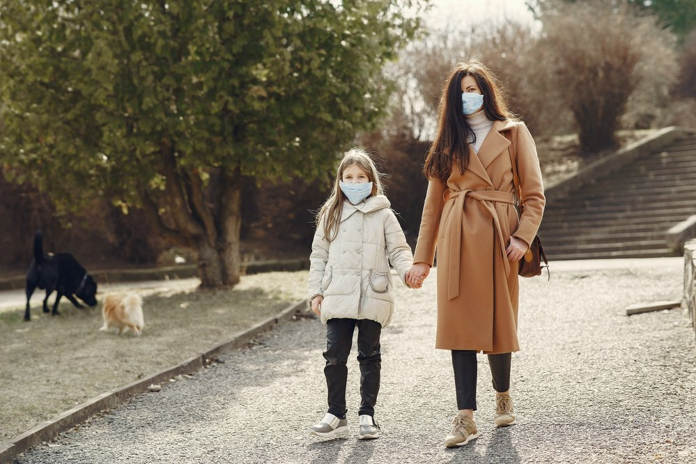 mother and daughter walking with face masks