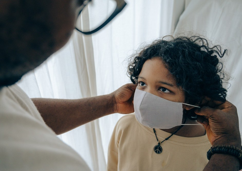 parent putting face mask on child - COVID 19