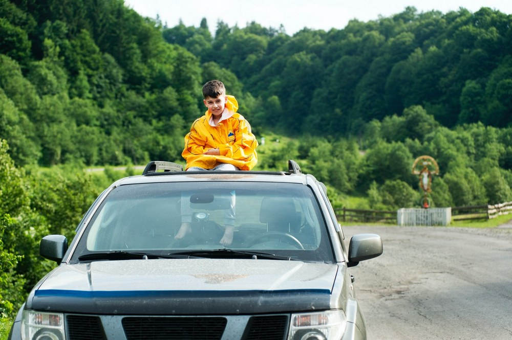 kid sitting on car rooftop