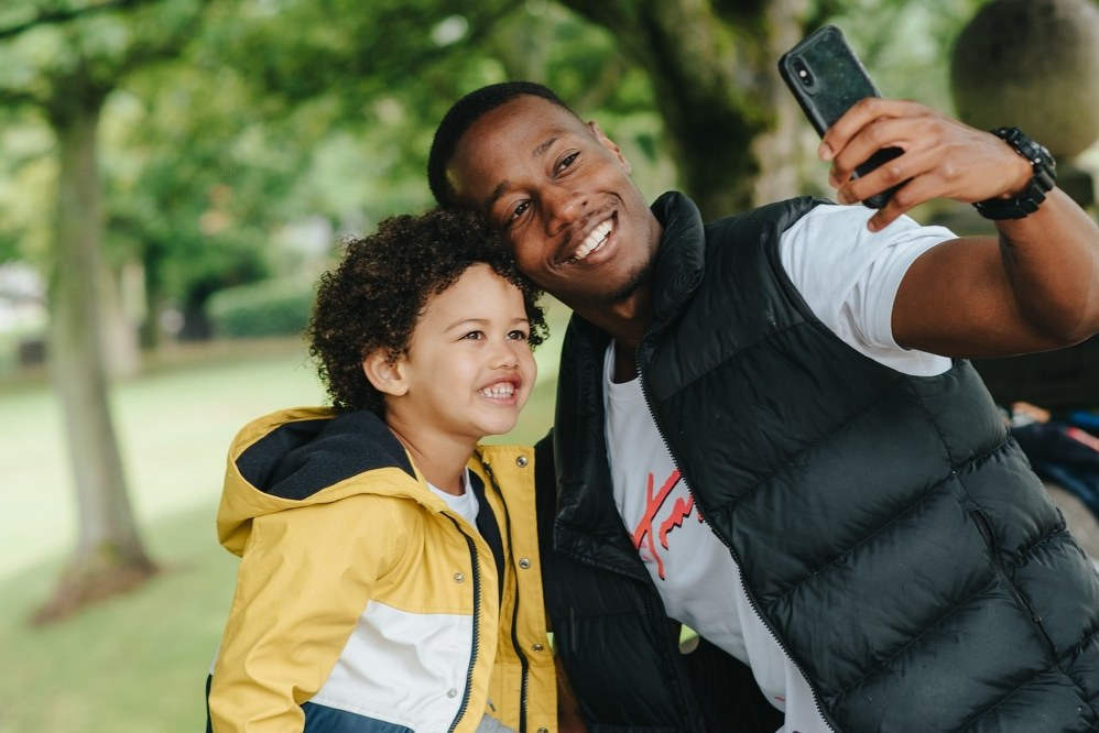 father and son taking selfie on city trip
