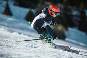 kid racing down the slope on ski holiday