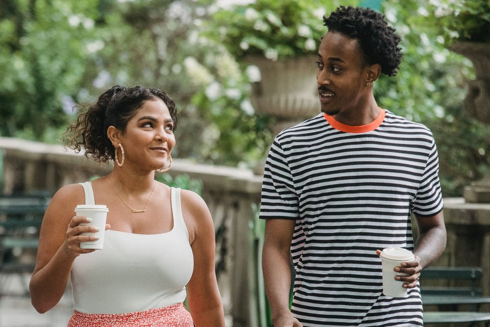 couple smile at each with coffee in hand other on walk