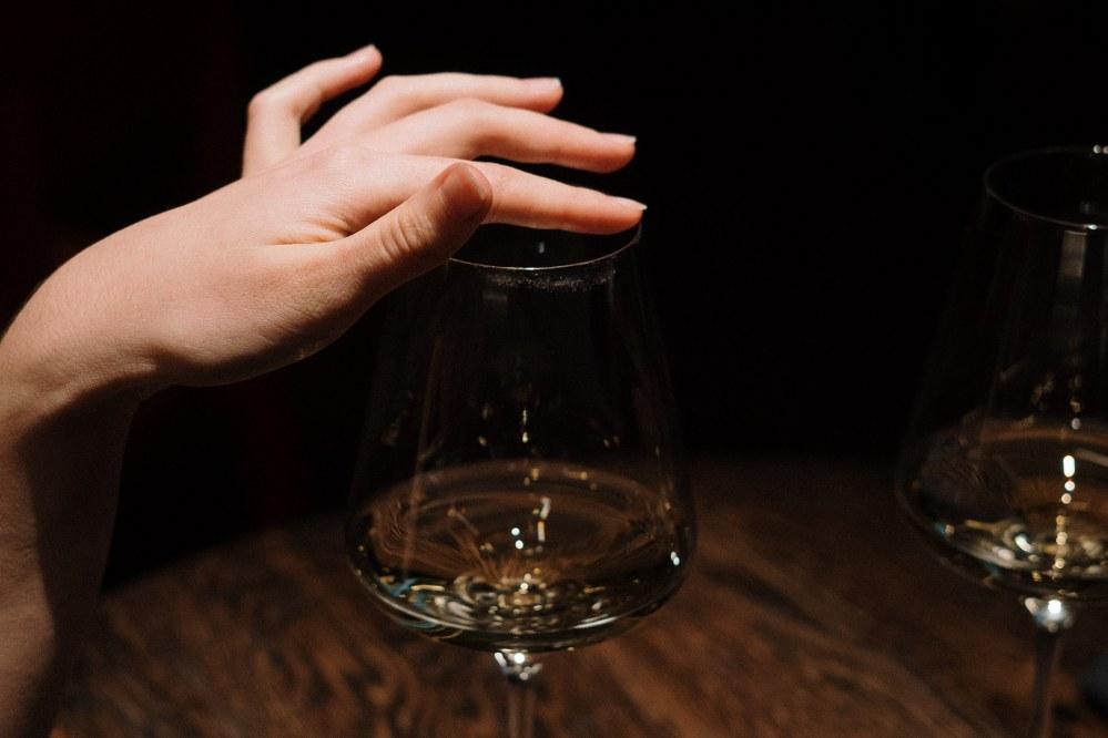 woman touching rim of her wine glass