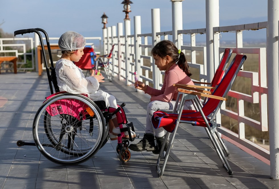 girl in wheelchair on holiday playing with sister