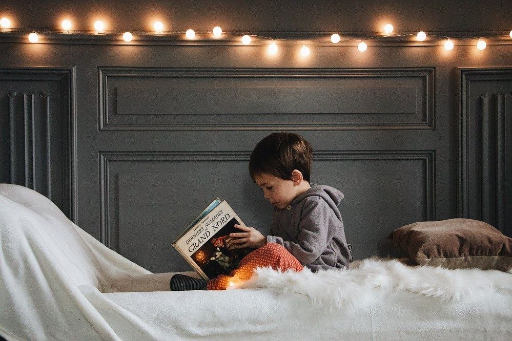 boy reading in bed with fairy lights